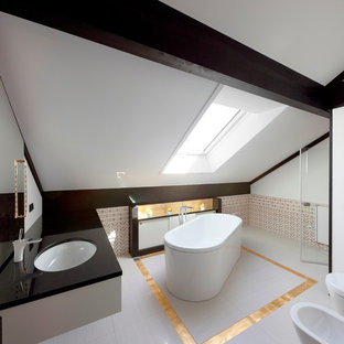 This is an example of a large eclectic bathroom in Stuttgart with a freestanding tub, a bidet, multi-coloured tile, white walls and an undermount sink.