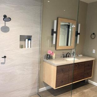 サクラメントの中サイズのコンテンポラリースタイルのおしゃれなマスターバスルーム (家具調キャビネット、濃色木目調キャビネット、アルコーブ型浴槽、オープン型シャワー、壁掛け式トイレ、ベージュのタイル、石スラブタイル、ベージュの壁、磁器タイルの床、壁付け型シンク、珪岩の洗面台、ベージュの床、オープンシャワー、ベージュのカウンター) の写真