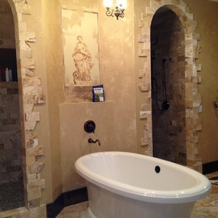 This is an example of a large mediterranean ensuite bathroom in Orlando with a freestanding bath, a double shower, yellow tiles, stone tiles, multi-coloured walls and travertine flooring.