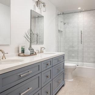 Ispirazione per una stanza da bagno costiera di medie dimensioni con ante in stile shaker, ante blu, vasca/doccia, WC monopezzo, piastrelle grigie, pareti bianche, pavimento beige e porta doccia scorrevole