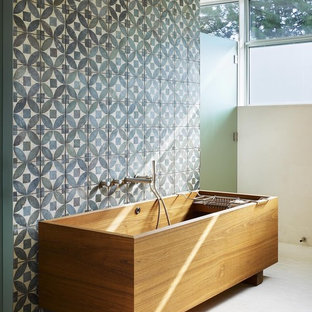 This is an example of a medium sized contemporary ensuite bathroom in Toronto with a freestanding bath, blue tiles, stone tiles, blue walls and mosaic tile flooring.