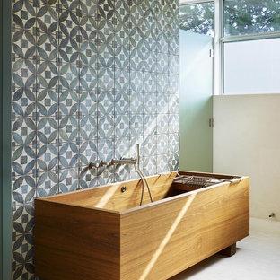 Réalisation d'une salle de bain principale design de taille moyenne avec une baignoire indépendante, un carrelage bleu, un carrelage de pierre, un mur bleu et un sol en carrelage de terre cuite.