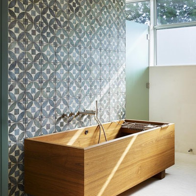 Mid-sized trendy master blue tile and stone tile mosaic tile floor freestanding bathtub photo in Toronto with blue walls