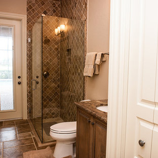 Design ideas for a small mediterranean shower room in Miami with raised-panel cabinets, dark wood cabinets, beige tiles, beige walls, travertine flooring, a submerged sink, granite worktops, brown floors, a hinged door and grey worktops.
