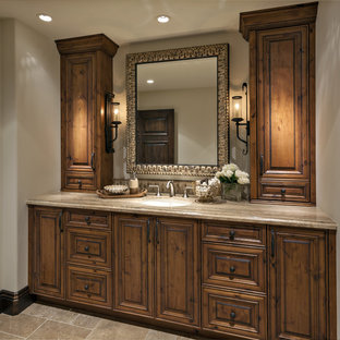 Inspiration for a mid-sized mediterranean 3/4 black tile and stone tile travertine floor and beige floor bathroom remodel in Phoenix with raised-panel cabinets, medium tone wood cabinets, white walls, an undermount sink, granite countertops and gray countertops