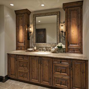 Foto di una stanza da bagno con doccia mediterranea di medie dimensioni con ante con bugna sagomata, ante in legno scuro, piastrelle nere, piastrelle in pietra, pareti bianche, pavimento in travertino, lavabo sottopiano, top in granito, pavimento beige e top grigio