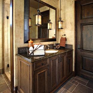 Неиссякаемый источник вдохновения для домашнего уюта: ванная комната среднего размера в средиземноморском стиле с врезной раковиной, фасадами с утопленной филенкой, темными деревянными фасадами, столешницей из гранита, душем в нише, бежевыми стенами, полом из сланца, душевой кабиной, металлической плиткой, серой плиткой, серым полом, унитазом-моноблоком и душем с распашными дверями