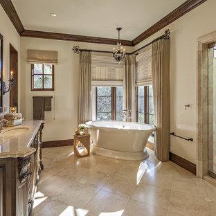 Inspiration pour une douche en alcôve méditerranéenne avec un placard en trompe-l'oeil, des portes de placard en bois sombre, une baignoire indépendante, un carrelage beige, un mur beige, un lavabo encastré, un sol beige et une cabine de douche à porte battante.