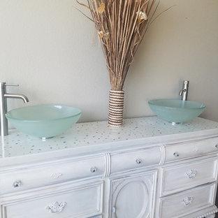 Modelo de cuarto de baño romántico con armarios tipo mueble, puertas de armario blancas, lavabo sobreencimera y encimera de cemento