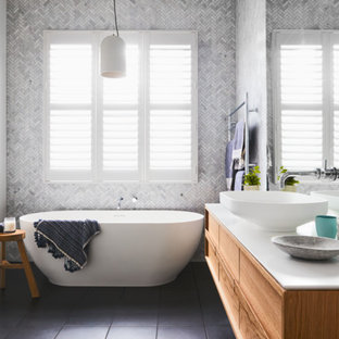 Photo of a traditional bathroom in Melbourne with flat-panel cabinets, medium wood cabinets, a freestanding bath, white walls, a vessel sink and grey floors.