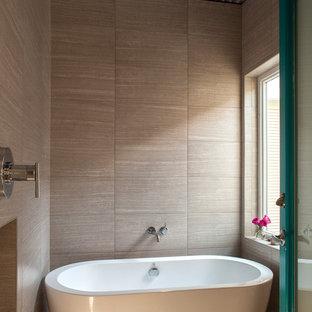 Свежая идея для дизайна: большая главная ванная комната в стиле лофт с отдельно стоящей ванной, открытым душем, бежевой плиткой, душем с распашными дверями, керамогранитной плиткой и бетонным полом - отличное фото интерьера