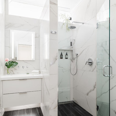 Example of a mid-sized trendy 3/4 porcelain tile and white tile porcelain tile and black floor walk-in shower design in Boston with flat-panel cabinets, white cabinets, white walls, an integrated sink, solid surface countertops, a hinged shower door and white countertops