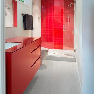 Inredning av ett modernt röd rött badrum med dusch, med släta luckor, röda skåp, en dusch i en alkov, röd kakel, vita väggar, ett undermonterad handfat, vitt golv och dusch med gångjärnsdörr