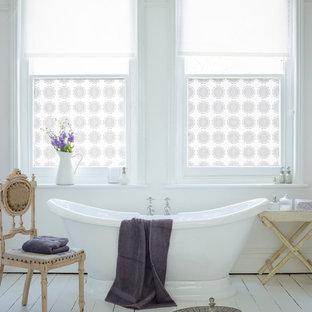 Diseño de cuarto de baño romántico con bañera exenta y suelo de madera pintada