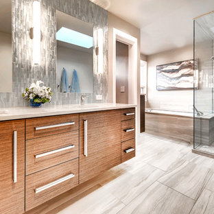 Inspiration for a contemporary master gray tile gray floor corner shower remodel in Denver with flat-panel cabinets, medium tone wood cabinets, an undermount tub, an undermount sink, a hinged shower door and beige countertops