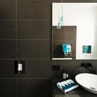 Modelo de cuarto de baño principal, de estilo americano, de tamaño medio, con armarios con paneles lisos, puertas de armario blancas, sanitario de pared, baldosas y/o azulejos negros, baldosas y/o azulejos de cerámica, paredes negras y encimera de granito