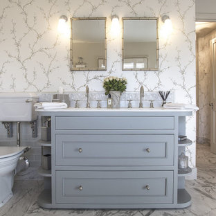 This is an example of a classic ensuite bathroom in London with recessed-panel cabinets, grey cabinets, a two-piece toilet, grey tiles, metro tiles, multi-coloured walls, marble flooring, a submerged sink, grey floors, white worktops, double sinks, a built in vanity unit and wallpapered walls.