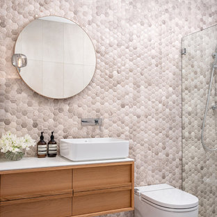 Contemporary bathroom in Sydney with medium wood cabinets, a curbless shower, a two-piece toilet, beige tile, mosaic tile, beige walls, a vessel sink, grey floor and white benchtops.