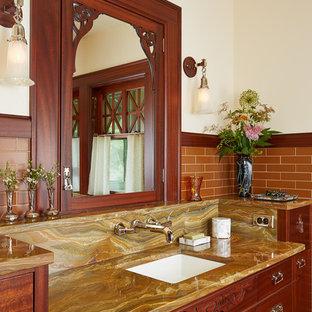 Modelo de cuarto de baño principal, de estilo americano, con lavabo bajoencimera, puertas de armario de madera oscura, paredes blancas, armarios con paneles lisos, encimera de granito, baldosas y/o azulejos naranja y baldosas y/o azulejos de cemento
