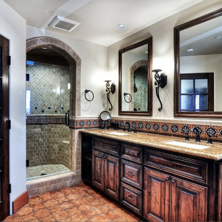 Photo of a medium sized mediterranean ensuite bathroom in Orange County with raised-panel cabinets, brown cabinets, a corner shower, beige tiles, mosaic tiles, white walls, porcelain flooring, a submerged sink, granite worktops, brown floors and a hinged door.