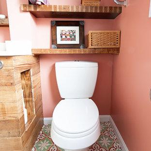 Cette photo montre une petit salle d'eau nature avec un lavabo encastré, un placard en trompe-l'oeil, des portes de placard en bois brun, un plan de toilette en marbre, une baignoire encastrée, un combiné douche/baignoire, un WC séparé, un carrelage blanc, des carreaux de céramique, béton au sol et un mur rose.