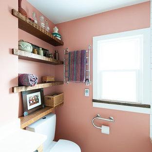 Diseño de cuarto de baño con ducha, de estilo de casa de campo, pequeño, con lavabo bajoencimera, puertas de armario de madera oscura, encimera de mármol, bañera encastrada sin remate, combinación de ducha y bañera, sanitario de dos piezas, baldosas y/o azulejos blancos, baldosas y/o azulejos de cerámica, suelo de cemento, armarios tipo mueble y paredes rosas