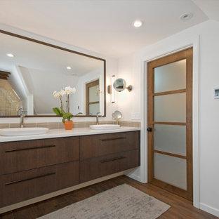 Idéer för att renovera ett stort funkis vit vitt en-suite badrum, med släta luckor, skåp i mörkt trä, ett fristående badkar, en toalettstol med hel cisternkåpa, beige kakel, porslinskakel, vita väggar, ett fristående handfat, bänkskiva i kvartsit och vitt golv