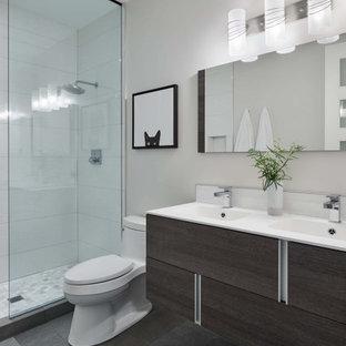 Exempel på ett mellanstort modernt vit vitt badrum, med släta luckor, skåp i mörkt trä, en dusch i en alkov, en toalettstol med separat cisternkåpa, grå kakel, porslinskakel, grå väggar, betonggolv, ett integrerad handfat, bänkskiva i akrylsten, grått golv och med dusch som är öppen