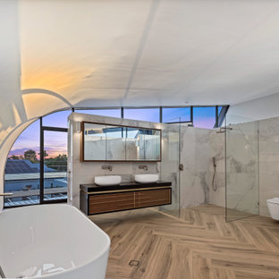Inspiration for an expansive contemporary master bathroom in Sunshine Coast with a freestanding tub, a corner shower, a wall-mount toilet, white tile, porcelain tile, white walls, porcelain floors, a vessel sink, engineered quartz benchtops, beige floor, an open shower, black benchtops, a double vanity, a floating vanity, vaulted, flat-panel cabinets and medium wood cabinets.