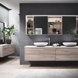 На фото: главная ванная комната среднего размера в стиле модернизм с плоскими фасадами, светлыми деревянными фасадами, угловой ванной, серой плиткой, плиткой из известняка, полом из плитки под дерево, настольной раковиной, столешницей из ламината, тумбой под две раковины и подвесной тумбой с