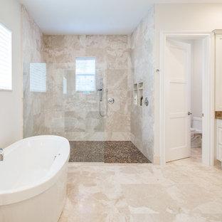 Esempio di un'ampia stanza da bagno padronale classica con lavabo sottopiano, ante con bugna sagomata, ante bianche, top in marmo, vasca freestanding, doccia a filo pavimento, WC monopezzo, piastrelle beige, piastrelle in pietra, pareti beige e pavimento in travertino