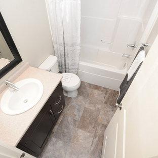 Ispirazione per una piccola stanza da bagno padronale minimal con ante in stile shaker, ante in legno bruno, vasca ad alcova, vasca/doccia, WC a due pezzi, pareti beige, pavimento in linoleum e lavabo da incasso