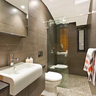 Ispirazione per una stanza da bagno con doccia contemporanea con ante lisce, ante in legno bruno, doccia a filo pavimento, WC monopezzo, pareti marroni, lavabo integrato, piastrelle marroni e porta doccia scorrevole