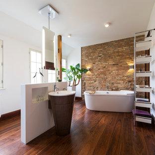 Imagen de cuarto de baño actual, extra grande, con puertas de armario de madera en tonos medios, bañera exenta, paredes blancas, suelo de madera oscura, lavabo con pedestal y encimera de madera