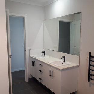 Immagine di una grande stanza da bagno padronale minimalista con ante bianche, doccia doppia, piastrelle bianche, lavabo da incasso e top bianco