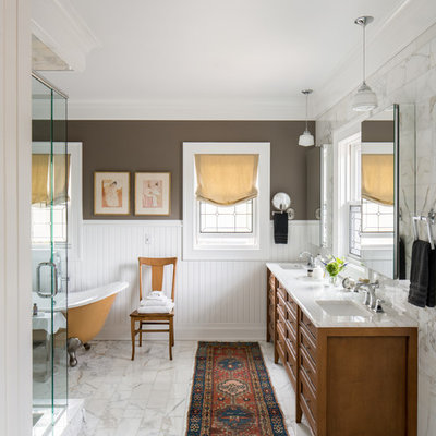Example of a classic master marble floor and white floor claw-foot bathtub design in Denver with furniture-like cabinets, medium tone wood cabinets, brown walls, an undermount sink and white countertops