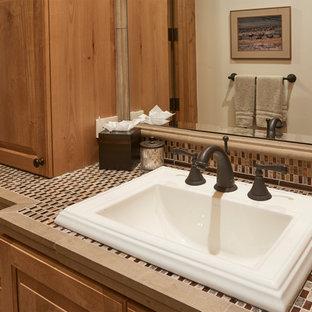 デンバーの中サイズのラスティックスタイルのおしゃれな浴室 (中間色木目調キャビネット、アルコーブ型浴槽、シャワー付き浴槽、ベージュのタイル、石タイル、ベージュの壁、オーバーカウンターシンク、ベージュの床、引戸のシャワー、ベージュのカウンター) の写真