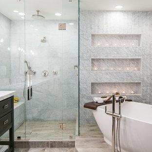 デンバーの中サイズのトランジショナルスタイルのおしゃれなマスターバスルーム (分離型トイレ、グレーのタイル、大理石タイル、グレーの壁、磁器タイルの床、アンダーカウンター洗面器、珪岩の洗面台、グレーの床、開き戸のシャワー、家具調キャビネット、黒いキャビネット、置き型浴槽、段差なし) の写真