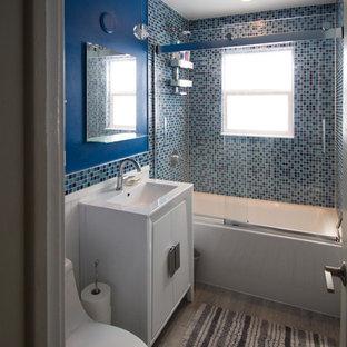Esempio di una piccola stanza da bagno padronale eclettica con ante lisce, ante bianche, vasca ad alcova, vasca/doccia, WC monopezzo, piastrelle blu, piastrelle di vetro, pareti blu, pavimento in gres porcellanato, lavabo sottopiano, top in quarzo composito, pavimento grigio e porta doccia scorrevole