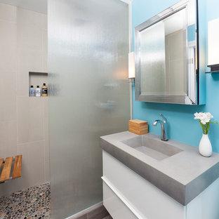 Diseño de cuarto de baño actual, pequeño, con lavabo integrado, armarios con paneles lisos, puertas de armario blancas, ducha abierta, paredes azules, baldosas y/o azulejos de porcelana, suelo de baldosas de porcelana, encimera de cemento, baldosas y/o azulejos grises y ducha abierta
