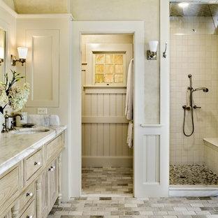 Immagine di una stanza da bagno chic con lavabo sottopiano, ante con riquadro incassato, ante in legno chiaro, doccia alcova, piastrelle beige, piastrelle in pietra e pavimento beige