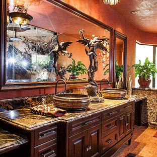 Выдающиеся фото от архитекторов и дизайнеров интерьера: большая главная ванная комната в средиземноморском стиле с фасадами островного типа, темными деревянными фасадами, гидромассажной ванной, угловым душем, оранжевыми стенами, полом из керамической плитки, настольной раковиной, столешницей из гранита, оранжевым полом, душем с распашными дверями и разноцветной столешницей