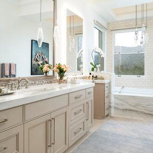 Klassisk inredning av ett flerfärgad flerfärgat en-suite badrum, med luckor med infälld panel, beige skåp, ett platsbyggt badkar, vit kakel, tunnelbanekakel, vita väggar, ett undermonterad handfat och beiget golv