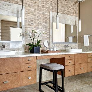 Idée de décoration pour une grande salle de bain principale sud-ouest américain avec un placard à porte plane, des portes de placard en bois brun, un carrelage de pierre, un sol en calcaire, une vasque, un plan de toilette en quartz, un sol beige, un plan de toilette blanc, un carrelage beige et un mur marron.