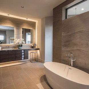 Immagine di una grande stanza da bagno padronale design con ante lisce, ante in legno bruno, vasca freestanding, piastrelle in gres porcellanato, pareti beige, pavimento in gres porcellanato, lavabo da incasso, pavimento grigio e top grigio