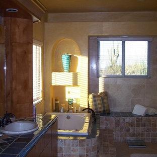 Ispirazione per una grande stanza da bagno padronale stile americano con ante lisce, ante in legno bruno, vasca da incasso, piastrelle multicolore, piastrelle in pietra, pareti beige, pavimento in gres porcellanato, lavabo da incasso, top piastrellato e pavimento marrone