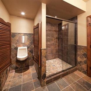 Foto på ett stort vintage badrum, med en dusch i en alkov, ett urinoar, stenkakel, beige väggar, skiffergolv och brun kakel