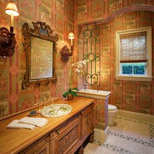 Diseño de cuarto de baño con ducha, mediterráneo, de tamaño medio, con armarios con paneles empotrados, puertas de armario marrones, sanitario de dos piezas, paredes multicolor, suelo de baldosas de cerámica, lavabo encastrado y encimera de madera