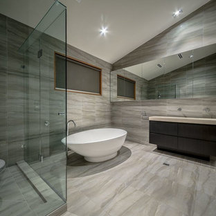 Photo of a mid-sized contemporary master bathroom in Melbourne with a freestanding tub, a corner shower, a one-piece toilet, porcelain tile, porcelain floors, a drop-in sink, flat-panel cabinets and dark wood cabinets.