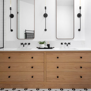 This is an example of a medium sized scandinavian family bathroom in Montreal with beaded cabinets, light wood cabinets, an alcove shower, a one-piece toilet, white tiles, ceramic tiles, white walls, mosaic tile flooring, a submerged sink, engineered stone worktops, black floors, a hinged door, white worktops, a wall niche, double sinks and a built in vanity unit.